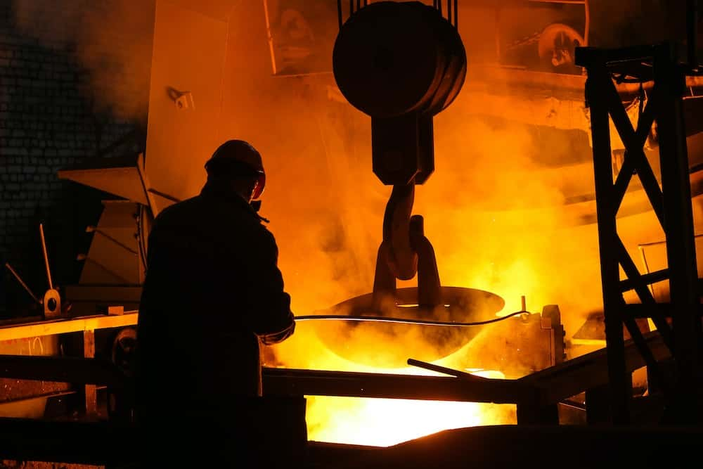North American foundry worker stands over molten metal.